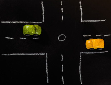 Green and Yellow wooden car toys stop on crossroad on chalk board Banque d'images
