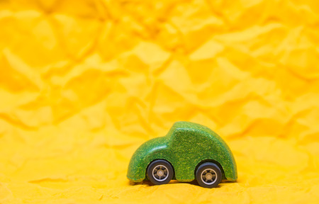 Isolated Green wooden car toy on Yellow crumpled paper background Banque d'images