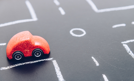 Red wooden car toy stop on crossroad on chalk board