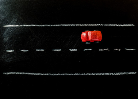 Red wooden car toy on the road of chalk board