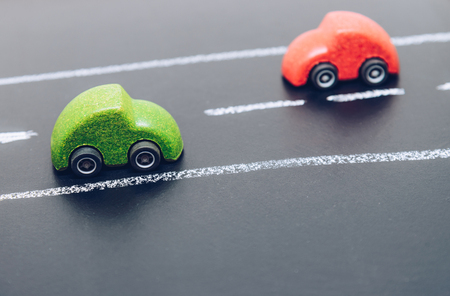 Red and Green wooden car toys drive on the road on chalk board