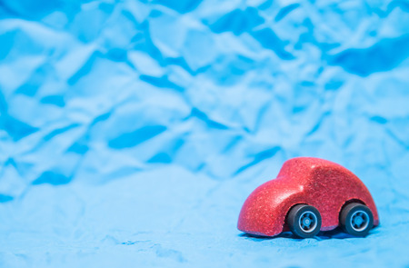 Isolated Red wooden car toy on Blue crumpled paper background