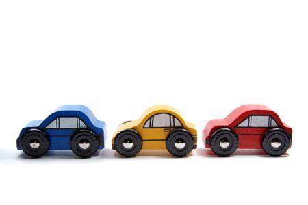 Trois simple jouet en bois dans une rangée de voitures, sur un fond blanc.