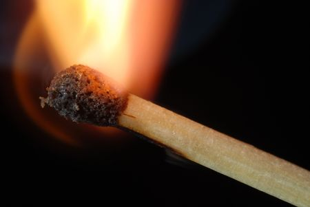 igniting: Close-up of igniting match isolated on black