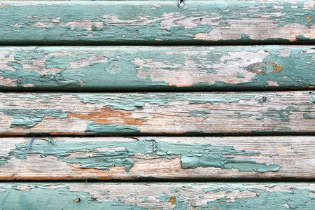 flaking: An old wooden wall texture with peeling faded green paint