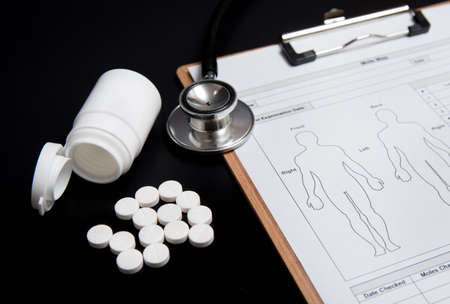 White pills and a white bottle, along with a stethoscope and a medical chart, are over a black background.