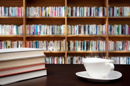 books stacked on the desk with a cup of coffee.