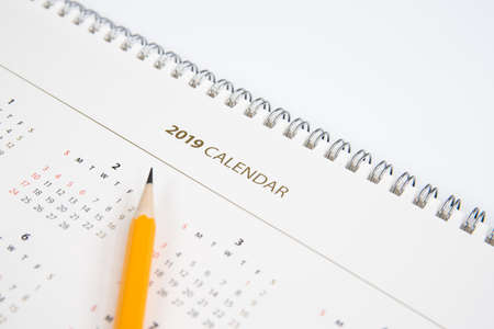 Desk calendar and yellow pencil on white background.