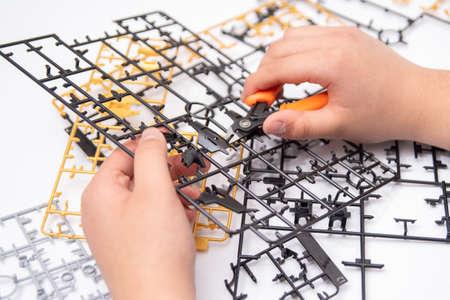 A boys hand assembling plastic models using tools.