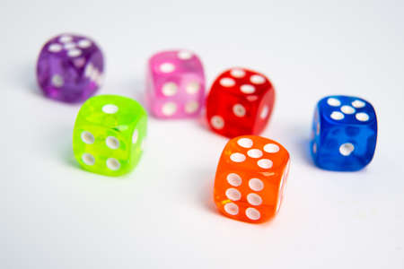 Dice of different colors isolated on a white background.