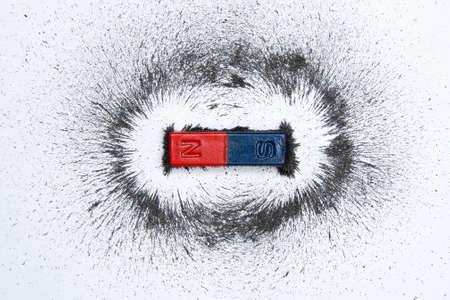 Magnete a barra con campo magnetico in polvere di ferro su sfondo bianco.