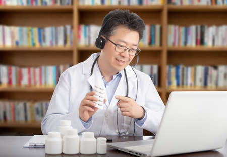 an Asian doctor who is remotely consulting with a patient. Telehealth concept.