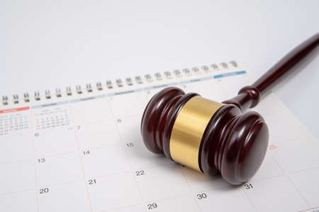 A wooden judge gavel and calendar isolated on white background.