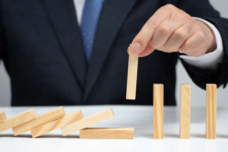 Male hand stopping the domino effect. Risk control concept. Stok Fotoğraf - 132929757