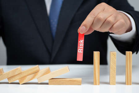 Male hand stopping the domino effect. Risk control concept. Stok Fotoğraf - 132929794