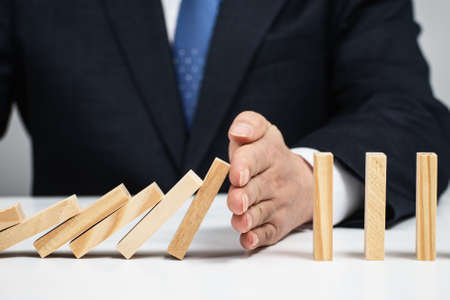 Male hand stopping the domino effect. Risk control concept. Stock fotó