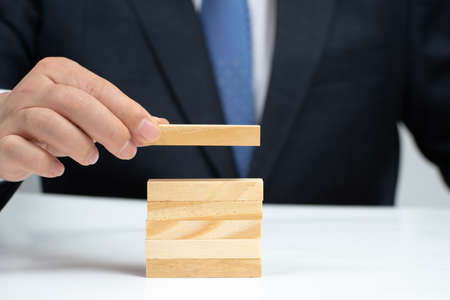 Hands of a businessman stacking wooden blocks on the table. Business concept.