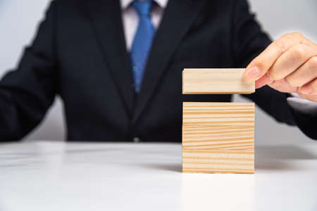 Hands of a businessman stacking wooden blocks on the table. Business concept. Stok Fotoğraf - 132928960