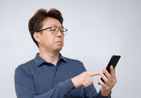Asian male trying to read something on his mobile phone. poor sight, presbyopia, myopia. Imagens