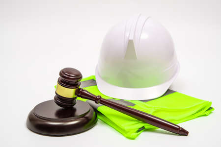 A labor-related legal concept with safety hats, work clothes, and a judge gavel on a white background.