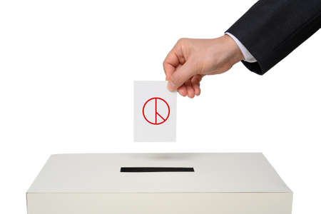 Mans hand down the ballot in the ballot box.