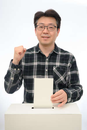 Man's hand down the ballot in the ballot box. Isolated on white background.
