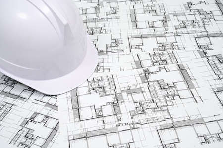 Construction industry concept with a hard hat on architectural drawing. Stock Photo