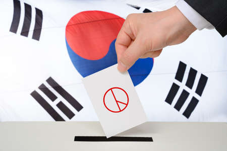 South Korea election concept. A man's hand with a ballot in a ballot box against the backdrop of a Korean flag