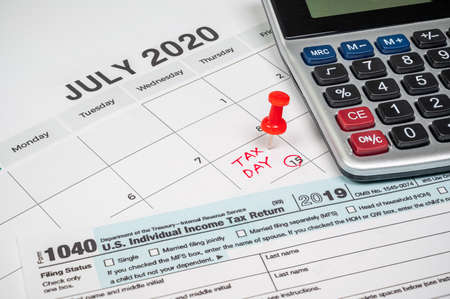 The tax day was extended to July 15th because of Covid-19. July calendar showing 1040 return form and tax day.