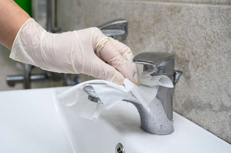 Disinfecting the bathroom. Faucet cleaning and disinfection. Prevention of coronavirus infection.