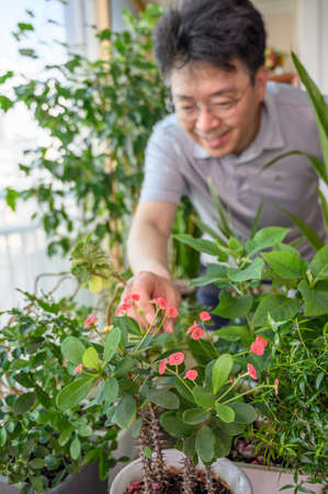 An Asian middle-aged man who smiles while taking care of a flower bed at home.