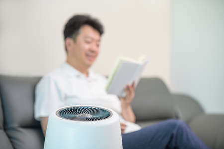 An Asian middle-aged man reading in the living room with an air purifier on. Blur background. Zdjęcie Seryjne
