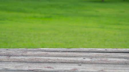 Wood deck and blur nature green grass background.