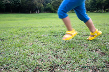 The legs of a child running on the lawn. Zdjęcie Seryjne
