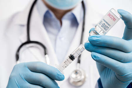 The doctor's hand wearing blue gloves against white background and holding Covid-19 vaccine.