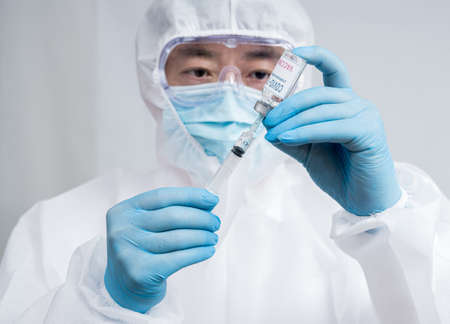 A male scientist wearing blue gloves and a protective suit holding a Covid-19 vaccine. 免版税图像