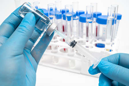 Scientists hand wearing blue gloves and holding an ampoule and syringe.