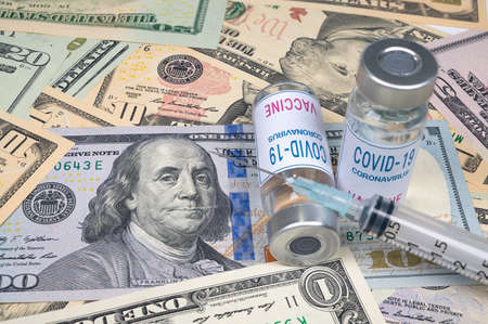 syringes and covid-19 vaccine ampoule lying on top of the US dollar.