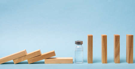 Vaccine concept with wood domino and ampoule on blue background. 免版税图像 - 152643032