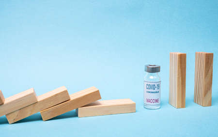 Vaccine concept with wood domino and COVID-19 vaccine ampoule on blue background.