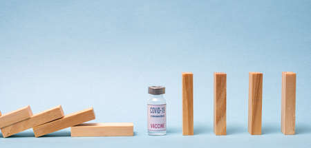 Vaccine concept with wood domino and COVID-19 vaccine ampoule on blue background. 免版税图像 - 152643034