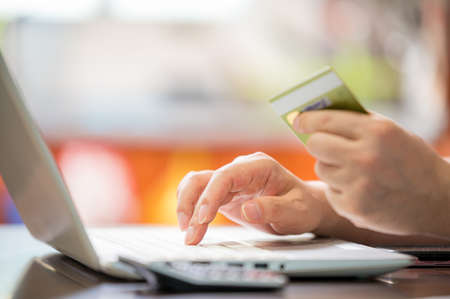 E-commerce concept. Mans hand holding a credit card in hand and entering data on a laptop 免版税图像 - 153330011
