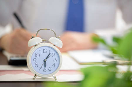 Working Businessman and White Alarm Clock. Work Time concept. 免版税图像