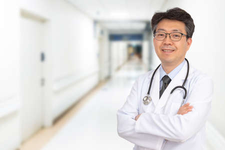 An Asian middle-aged male doctor smiling in the hospital corridor.