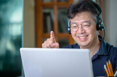 Middle-aged Asian man working at home. Telecommuting concept. 免版税图像 - 154716255