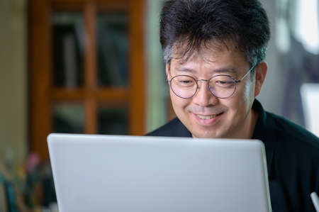 Middle-aged Asian man working at home. Telecommuting concept. 免版税图像 - 154716261