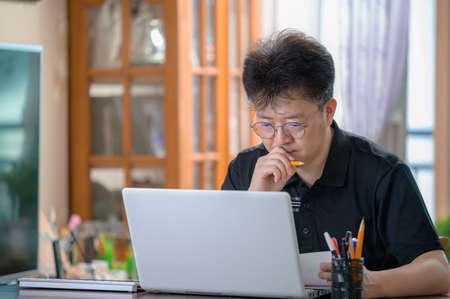 Middle-aged Asian man working at home. Telecommuting concept. 免版税图像 - 154716264