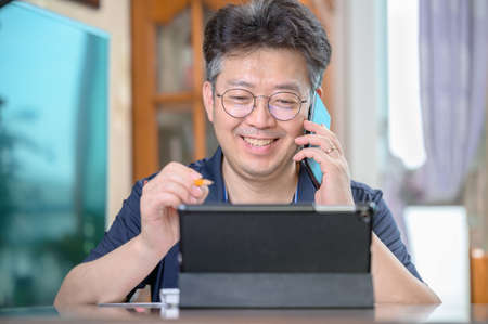 Middle-aged Asian man working at home. Telecommuting concept. 免版税图像 - 154716266