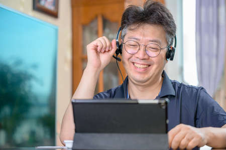 Middle-aged Asian man working at home. Telecommuting concept.