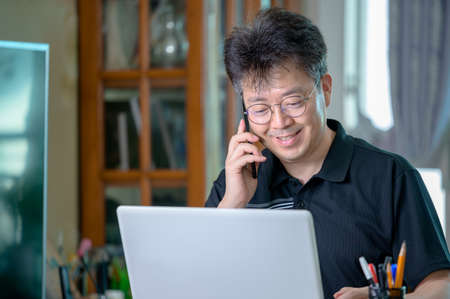 Middle-aged Asian man working at home. Telecommuting concept. 免版税图像 - 154716270